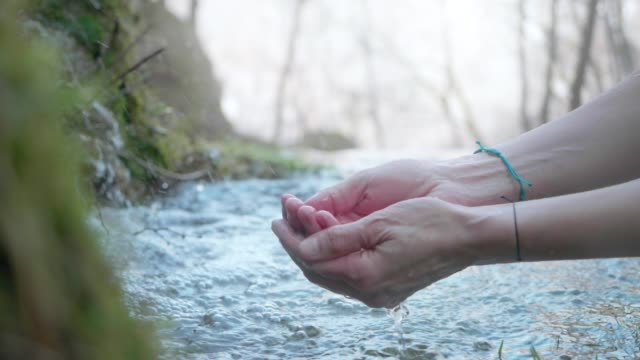 Hands With Pure Spring Water. Crystal Clear Mountain Water