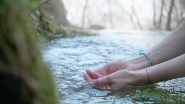 vídeos y material grabado en eventos de stock de manos con agua de manantial pura. agua cristalina de la montaña - riachuelo
