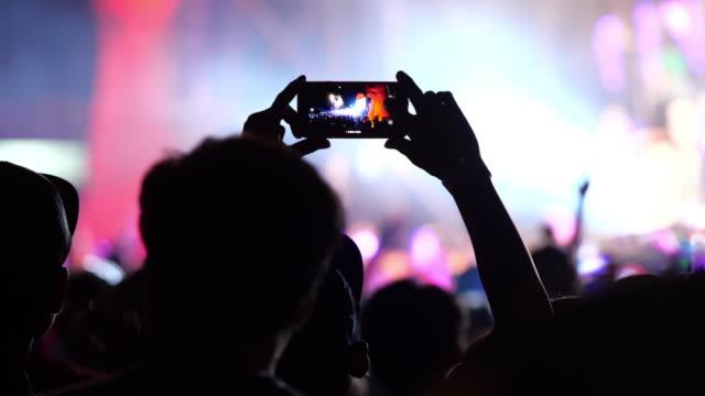 vídeos de stock, filmes e b-roll de mãos com os smartphones no concerto - rocking