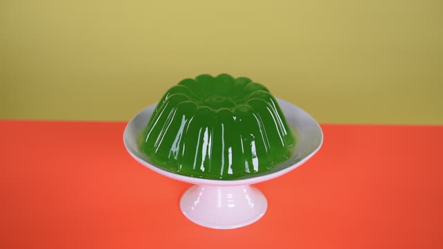 hands wobbling green jelly on cake stand - gelatin stock videos and b-roll footage