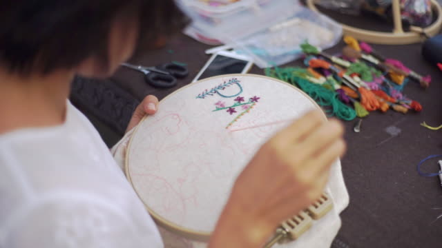 hands woman embroiders flowers on the hoop, handmade and handicraft concept. - artist's canvas stock videos & royalty-free footage