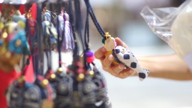 Hand van vrouwen met patchwork sleutelhanger souvenirs uit ambachtelijke productmarkt, hand gemaakt en ambachtelijke concept.