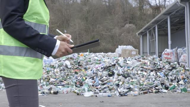 リサイクルセンターでタブレットに取り組む手。廃棄物分離工場で働くメンテナンスエンジニアのクローズアップ。 - 廃棄物処理点の映像素材/bロール