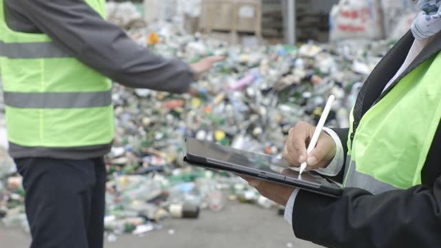 リサイクルセンターでタブレットに取り組む手。廃棄物分離工場で働くメンテナンスエンジニアのクローズアップ。 - リサイクル工場点の映像素材/bロール