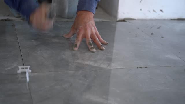 hands working placing ceramic floor tiles - building activity stock videos & royalty-free footage