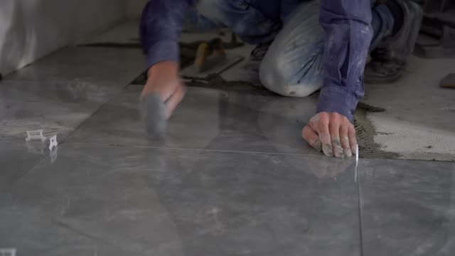 hands working placing ceramic floor tiles - installing stock videos & royalty-free footage