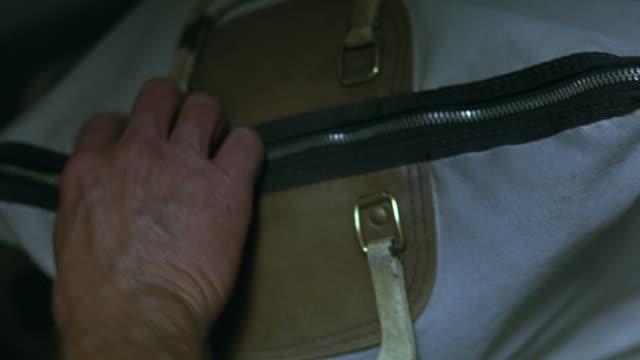 Hands zip open a money bag, and carry it away.