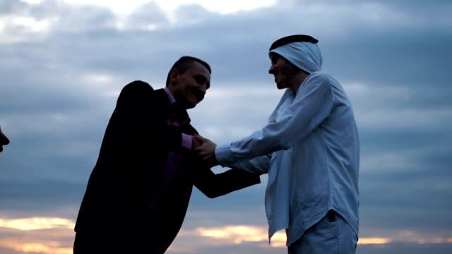 vídeos de stock, filmes e b-roll de handsake entre árabe sócio e pastor - oriente médio etnia