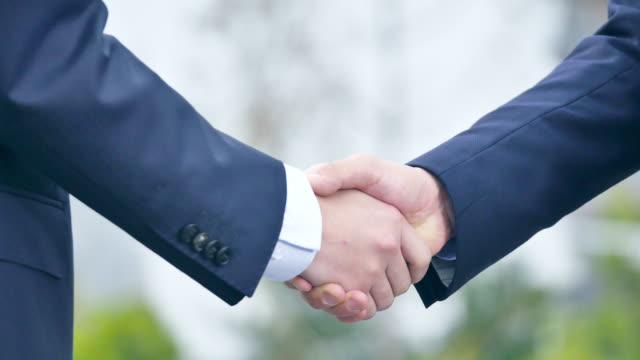 vídeos de stock, filmes e b-roll de aperto de mão entre empresários - parceria