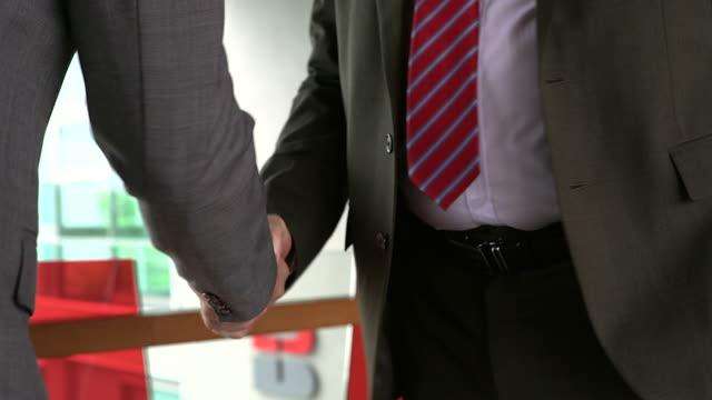 vidéos et rushes de poignée de main d'homme d'affaires, démontrant leur accord pour signer l'accord ou contrat entre leurs entreprises / sociétés / entreprises. - tenue d'affaires formelle