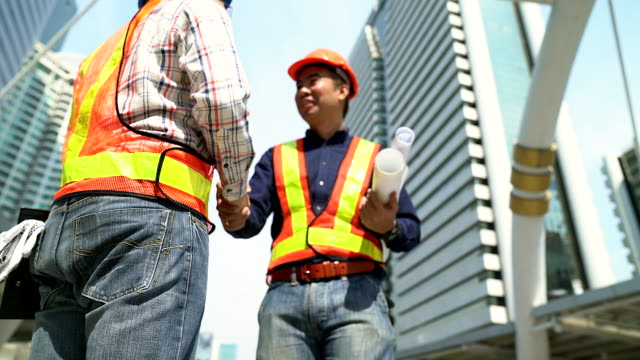 Handshake of engineers greeting at construction site with cityscape as background.