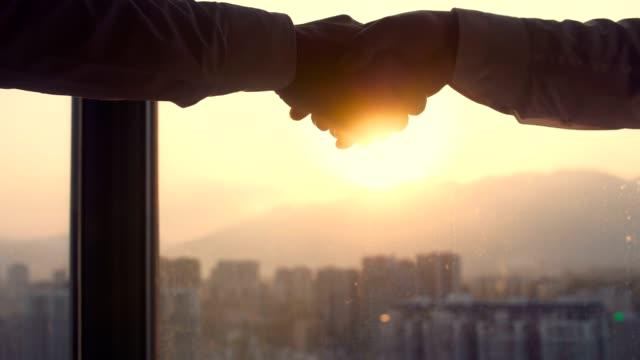 vidéos et rushes de poignée de main avec la lumière du soleil d'or - doigt humain