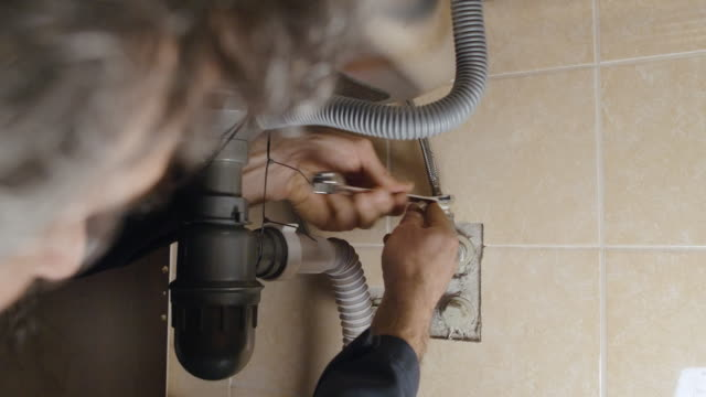 handsome active senior man repairing the sink in the kitchen. diy. home improvement. - rebuilding stock videos & royalty-free footage