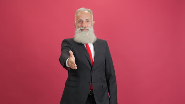 handsome adult businessman extends a hand for a handshake a red background - 50 59 years video stock e b–roll