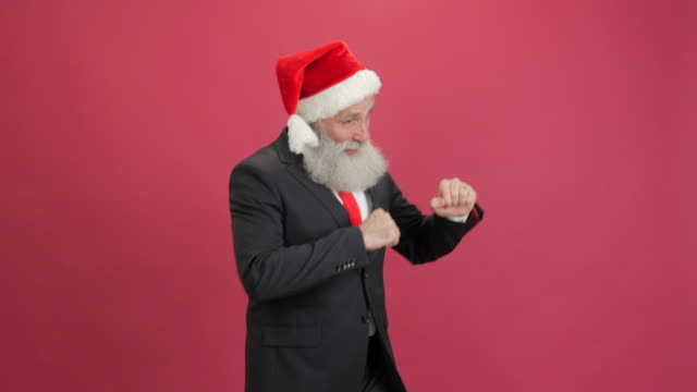 handsome adult businessman in the cap of santa showing copy space and showing thumbs up on red background - beard stock videos & royalty-free footage