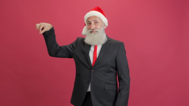 handsome adult businessman in the cap of santa showing copy space and showing thumbs up on red background - kharkov stock videos & royalty-free footage