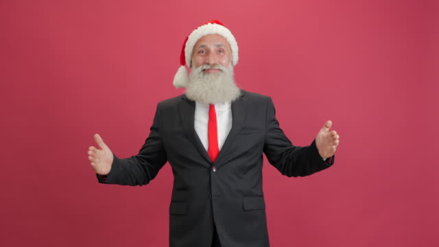 handsome adult businessman in the cap of santa showing copy space and showing thumbs up on red background - 50 59 years video stock e b–roll
