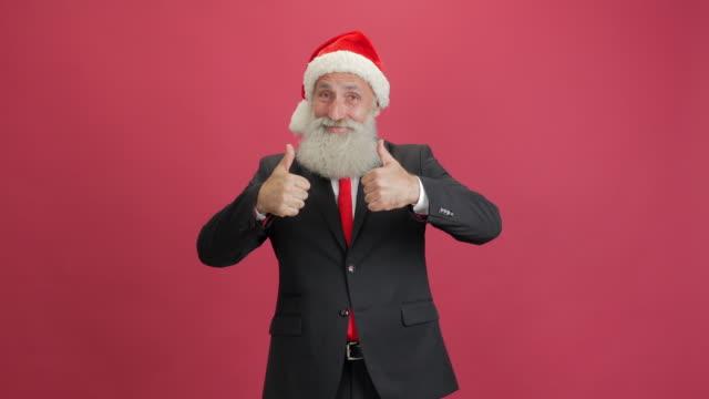schöne erwachsene geschäftsmann in der kappe des santa auftauchend daumen auf rotem grund - weihnachtsmütze stock-videos und b-roll-filmmaterial