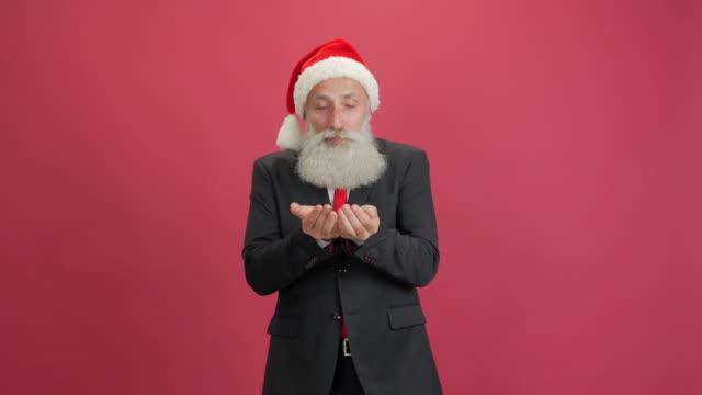 stilig vuxen affärsman i hatten för santa något blåser bort händerna på röd bakgrund - 50 59 years bildbanksvideor och videomaterial från bakom kulisserna