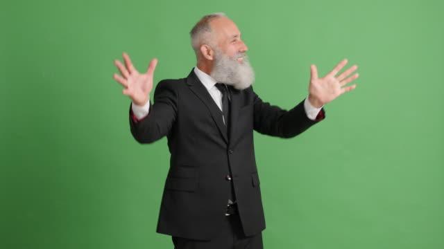 ein hübscher erwachsenen geschäftsmann präsentiert etwas auf grünem hintergrund - 50 59 years stock-videos und b-roll-filmmaterial
