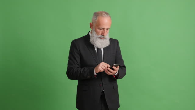 a handsome adult businessman is using a smartphone on a green background - solido video stock e b–roll