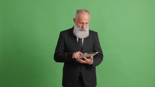 en stilig vuxen affärs man använder en tablett på en grön bakgrund - 50 59 years bildbanksvideor och videomaterial från bakom kulisserna