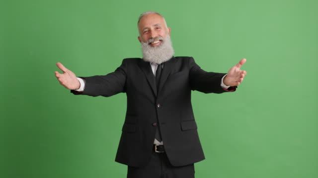 schöne erwachsene geschäftsmann öffnet seine arme um einen grünen hintergrund - 50 59 years stock-videos und b-roll-filmmaterial