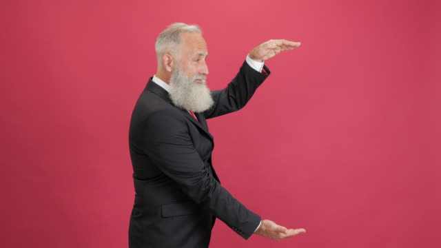 handsome adult businessman showing copy space and showing thumbs up on red background - 50 59 years video stock e b–roll