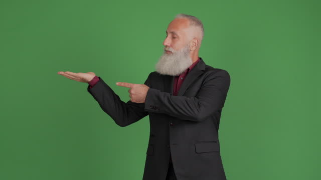 handsome adult businessman showing copy space and showing thumbs up on green background - big hair stock videos & royalty-free footage