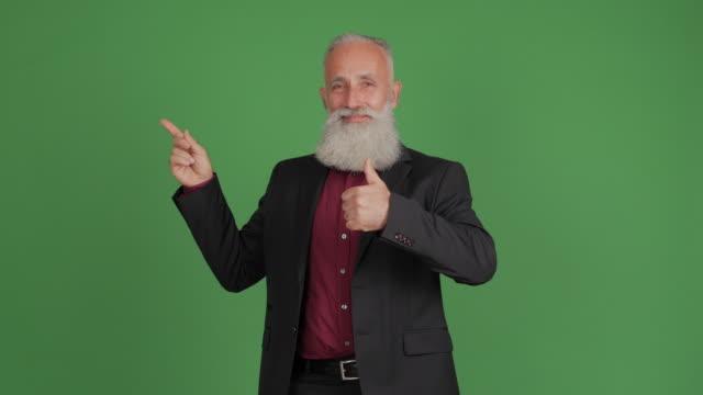 stilig vuxen affärsman visar kopia utrymme och visar tummen på grön bakgrund - 50 59 years bildbanksvideor och videomaterial från bakom kulisserna
