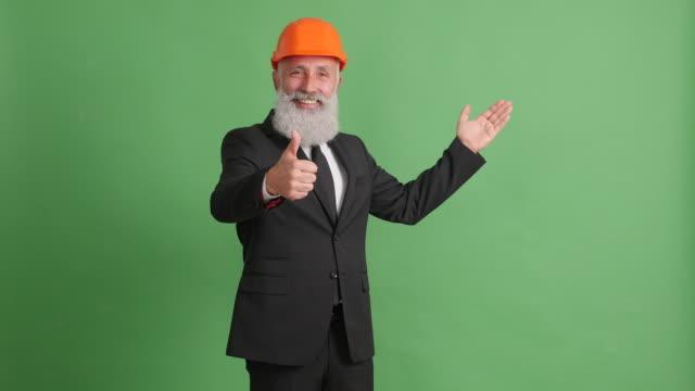 vídeos de stock, filmes e b-roll de espaço do empresário adulto bonito apresentando cópia e mostrando os polegares sobre fundo verde - 50 59 years