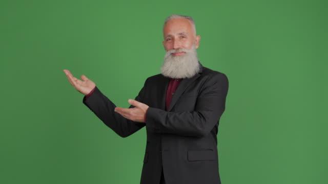 stilig vuxen affärsman visar kopia utrymme på grön bakgrund - 50 59 years bildbanksvideor och videomaterial från bakom kulisserna