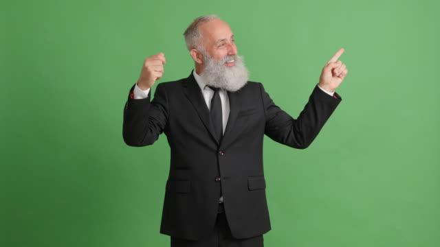vídeos de stock, filmes e b-roll de empresário de adulto bonito mostrando cópia espaço no plano de fundo verde - 50 59 years