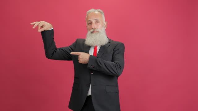 stilig vuxen affärsman visar kopia utrymme på röd bakgrund - 50 59 years bildbanksvideor och videomaterial från bakom kulisserna