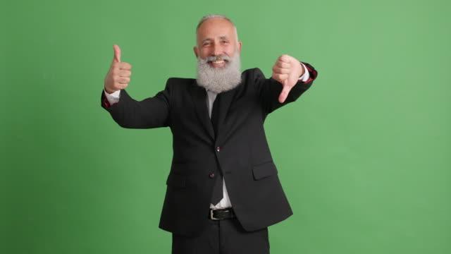 vídeos de stock, filmes e b-roll de empresário de adulto bonito mostrando polegares para cima e polegares para baixo sobre fundo verde - 50 59 years