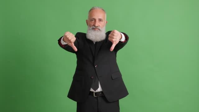 stilig vuxen affärsman visar tummen upp och tummen ner på grön bakgrund - 50 59 years bildbanksvideor och videomaterial från bakom kulisserna