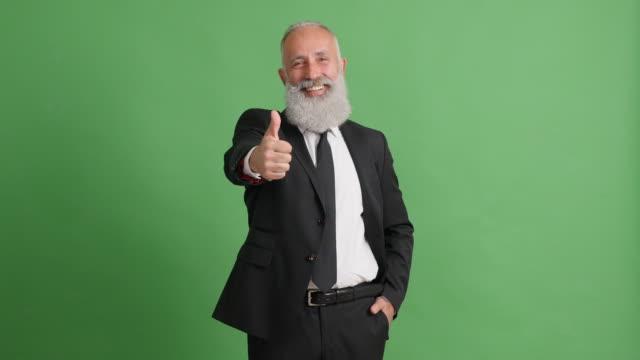 緑の背景の上に親指を表示ハンサムな大人のビジネスマン - 50 59 years点の映像素材/bロール