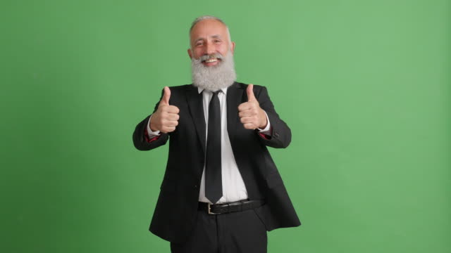 handsome adult businessman showing thumbs up on green background - big hair stock videos & royalty-free footage