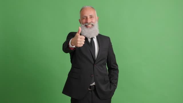 vídeos de stock, filmes e b-roll de empresário de adulto bonito mostrando os polegares sobre fundo verde - 50 59 years