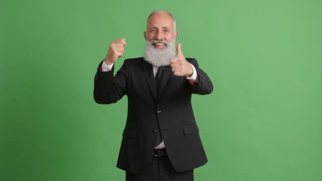 vídeos de stock, filmes e b-roll de lindo adulto empresário mostra algo em sua mão e mostra um polegar para sobre um fundo verde - 50 59 years