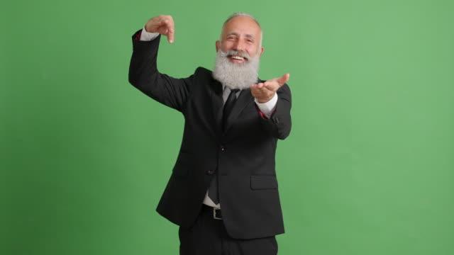 vídeos de stock, filmes e b-roll de lindo adulto empresário mostra algo na mão sobre um fundo verde - 50 59 years