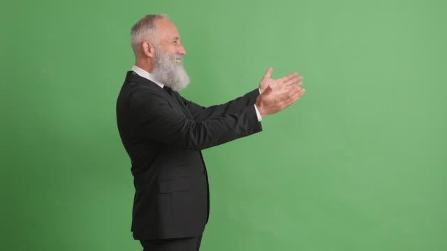 vídeos de stock, filmes e b-roll de lindo adulto empresário afavelmente estica as mãos em uma tela verde - 50 59 years