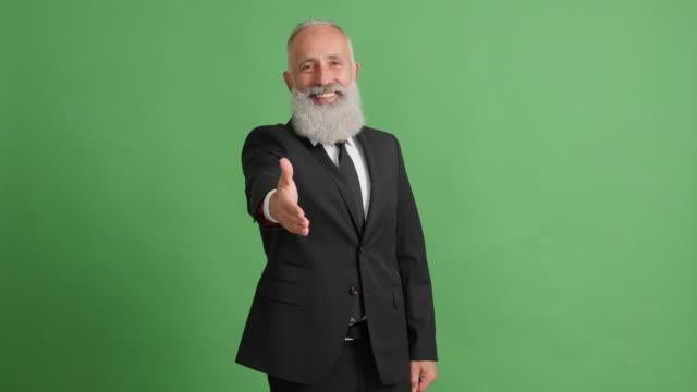 緑背景に握手を求めて手を伸ばしてハンサムな大人のビジネスマン - 50 59 years点の映像素材/bロール