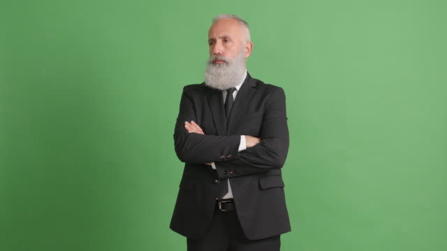 vídeos de stock, filmes e b-roll de lindo adulto empresário pensando em algo com as mãos cruzadas sobre um fundo verde - 50 59 years