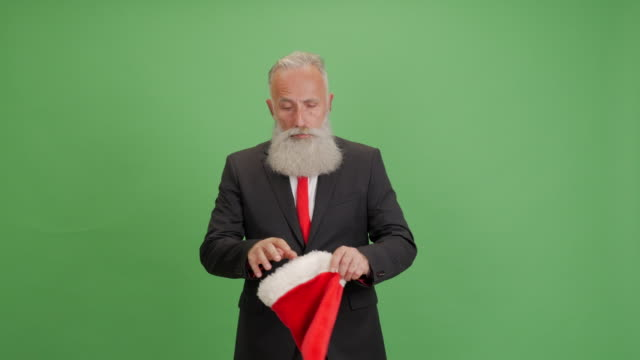handsome adult businessman wears a santa hat and rejoices on green background - big hair stock videos & royalty-free footage