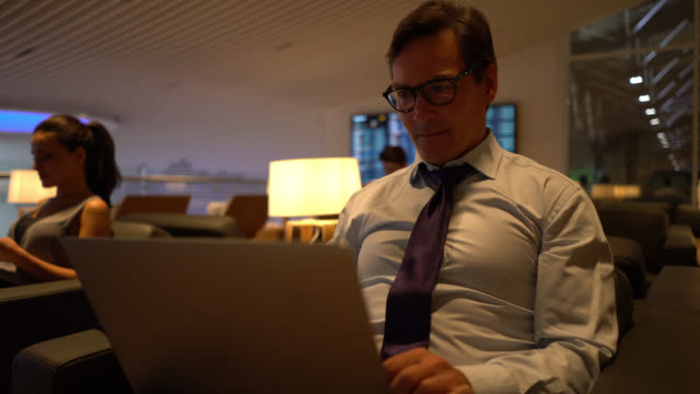 handsome adult businessman working on his laptop very focused at the airport's business lounge - gate stock videos & royalty-free footage