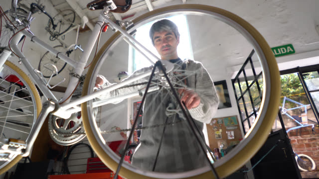 Handsome adult man adjusting a screw on the back wheel of a bike
