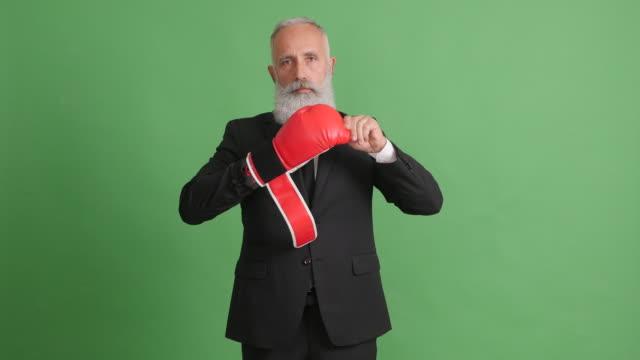 vídeos de stock, filmes e b-roll de um adulto bonito tira sua luva de boxe e estende uma mão sobre a tela verde - 50 59 years