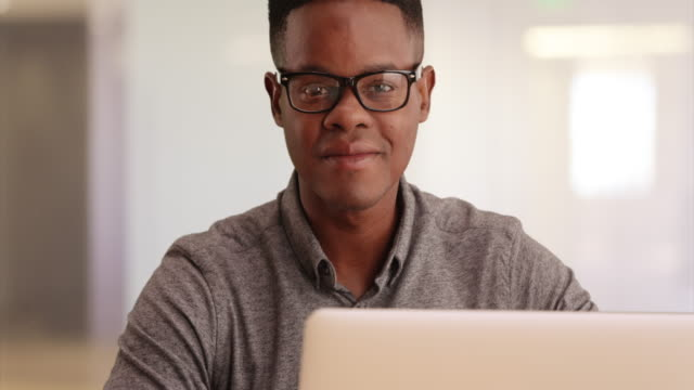 Handsome African American Millennial man sitting at desk with computer smiling