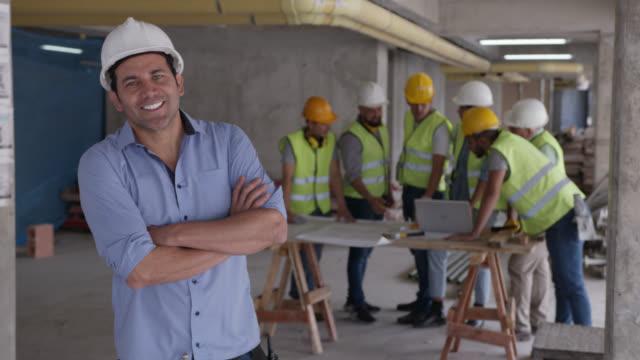 腕を組んだカメラに微笑む建設現場のハンサムな建築家のスーパーバイザー - 土木技師点の映像素材/bロール